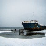 A rusting old boat on the snowy beach of the Bolshie Koty settlement