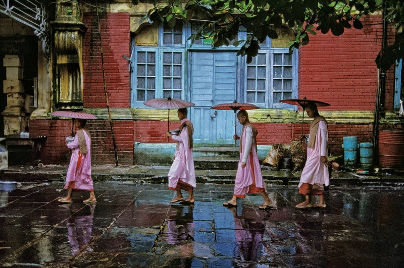 """Procession of Nuns, Rangoon, Burma, 1994 Procession of Nuns, Rangoon """"Each day these nuns walked a circuit around the city. McCurry asked if he could walk with them to make photographs. With their consent, he accompanied them for several days, searching for the best light and location. Even without their presence, this residential area could make a colourful image. With their presence, McCurry deliberately sought a rainy day in order to have some control over the level of color in the image. The line of their parasols echoes the yellow horizontal and creates the commentary of an adjacent hue upon the red brick."""" Bannon, Anthony. (2005). Steve McCurry. New York: Phaidon Press Inc, 29. Phaidon, Iconic Images, final book_iconic, page 8. Nuns in Yangon, Myanmar also rely on the local comunity- as did the Buddha himself. Pictures can offer themselves up to you - but only if you have patience. McCurry asked these nuns if he could follow them on their daily walk around the city. He trailed them for several days until, with rain falling and a brightly coloured building as a fitting backdrop, he captured this graceful image. National Geographic, Perry Garfinkel (December 2005). Buddha Rising: Out of the monastery, into the living room. National Geographic vol. 208(6) 88-109 Procession of nuns, Rangoon, Burma, 1994. Pg 212-213, Untold: The Stories Behind the Photographs. South Southeast_Book Steve Mccurry_Book Iconic_Book Untold_book final print_MACRO final print_Genoa final print_Sao Paulo final print_Birmingham final print_Milan Fine Art Print retouched_Sonny Fabbri 4/11/2013"""