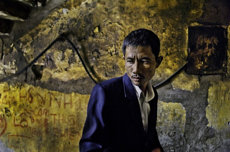 Nguyen Quoc Khanh in the stairwell of his tenement apartment, Viet Tri, Phu Tho province, Vietnam, 2007 Young man, Phu Tho Province, Vietnam, 2007 United Nations, Global Fund, Access to Life, final print_milan, Phaidon, Iconic Images, final book_iconic, iconic photographs In the stairwell of his apartment building, the man's smart attire belies the shambolic surroundings in which he resides. With electrical components haphazardly crawling along a damp flaky wall, the health and safety risks of his habitat are belittled by his, and subsequently our, intensely morose preoccupation, as this man is suffering from AIDS. Nguyen Quoc Khanh in the stairwell of his tenement apartment, Viet Tri, Phu Tho Province, Vietnam, 2007. Pg 250-251, Untold: The Stories Behind the Photographs. Magnum Photos, NYC107680, MCS2007003G10031 Phaidon, Iconic Images, final book_iconic, page 201 Iconic_Book