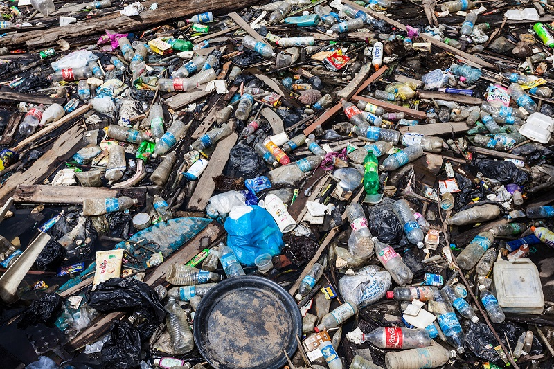 """Jakarta, Indonesia - August 16, 2012: Lots of garbage made of different material floating on the water in one of the water channel of the city"""